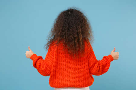 Back rear view of young african american girl in casual orange knitted clothes isolated on pastel blue wall background studio portrait. People lifestyle concept. Mock up copy space. Showing thumbs up.