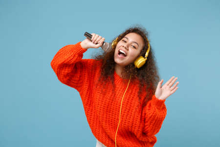 Cheerful young african american girl in orange knitted clothes isolated on pastel blue background. People lifestyle concept. Mock up copy space. Listen music with headphones, sing song in microphone. Stock Photo