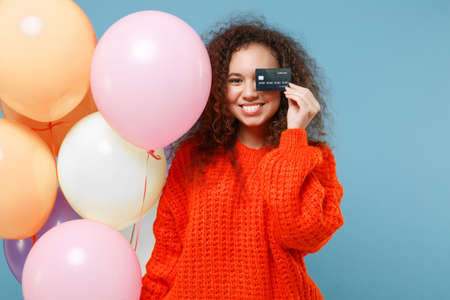 Smiling african american girl in orange knitted clothes isolated on pastel blue background. Birthday holiday party concept. Celebrating hold colorful air balloons covering eye with credit bank card.