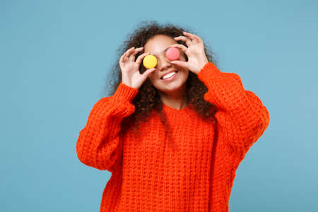 Funny young african american girl in casual orange knitted clothes isolated on pastel blue background studio portrait. People lifestyle concept. Mock up copy space. Covering eyes with french macarons.