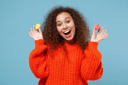Excited young african american girl in casual orange knitted clothes isolated on pastel blue background studio portrait. People emotions lifestyle concept. Mock up copy space. Hold french macarons.