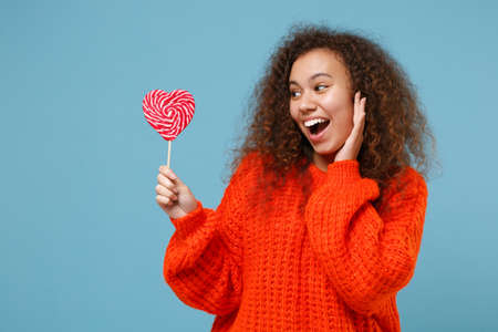 Excited young african american girl in casual orange knitted clothes isolated on pastel blue wall background studio portrait. People lifestyle concept. Mock up copy space. Hold heart lollipop candy.