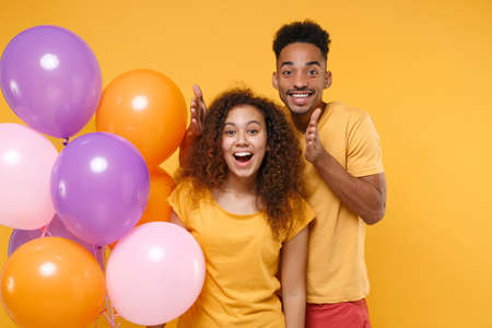 Surprised young friends couple african american guy girl in casual clothes isolated on yellow orange background. Birthday holiday party people emotions concept. Celebrating hold colorful air balloons. Stockfoto