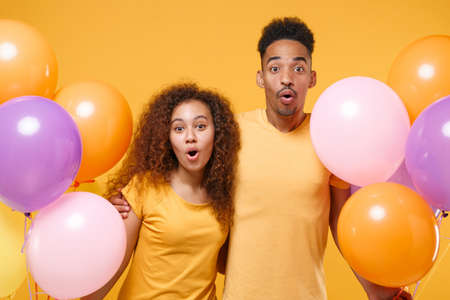 Shocked young friends couple african american guy girl in casual clothes isolated on yellow orange background. Birthday holiday party lifestyle concept. Celebrate hold colorful air balloons, hugging.