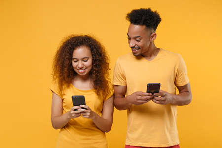Smiling young friends couple african american guy girl in casual clothes isolated on yellow orange background. People lifestyle concept. Mock up copy space. Using mobile phone, typing sms message.