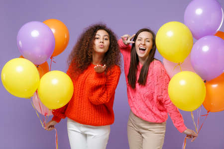 Funny european african american women friends in sweaters isolated on violet purple background. Birthday holiday party concept. Celebrate hold colorful air balloons send air kiss showing victory sign.