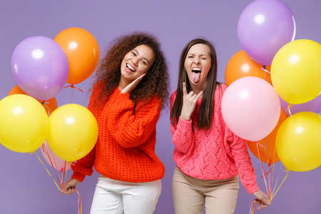 Funny european african american women friends in knitted sweaters isolated on violet purple background. Birthday holiday party concept. Celebrating hold colorful air balloons showing horns up gesture.