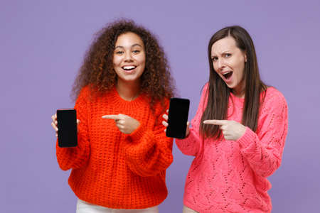 Cheerful two european african american women friends in knitted sweaters isolated on violet purple background. People lifestyle concept. Pointing index fingers on mobile phone with blank empty screen.