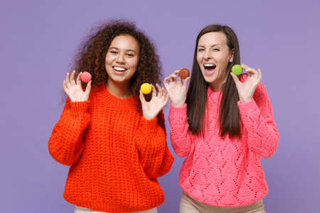 Cheerful two young european african american women friends in knitted sweaters isolated on violet purple background studio portrait. People emotions lifestyle concept. Hold colorful french macarons.
