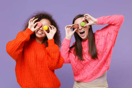 Funny two young european african american women friends in knitted sweaters isolated on violet purple background studio portrait. People lifestyle concept. Covering eyes with colorful french macarons.