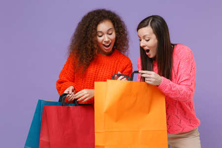 Shocked two young european african american women friends in knitted sweaters isolated on violet purple background in studio. People lifestyle concept. Hold package bag with purchases after shopping. Stock Photo