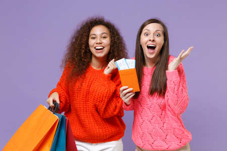 Surprised european african american women friends in knitted sweaters isolated on violet purple background. People lifestyle concept. Hold package bag with purchases after shopping, passport tickets. Imagens