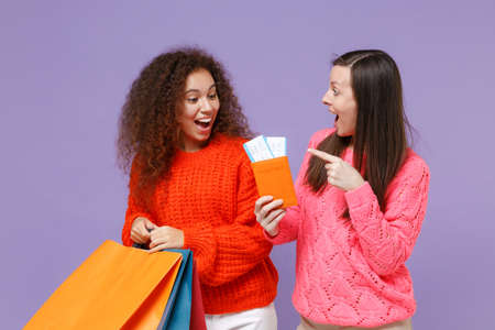 Shocked european african american women friends in knitted sweaters isolated on violet purple background. People lifestyle concept. Hold package bag with purchases after shopping, passport tickets.