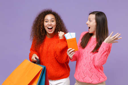 Excited european african american women friends in knitted sweaters isolated on violet purple background. People lifestyle concept. Hold package bag with purchases after shopping, passport tickets.