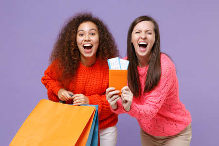Happy european african american women friends in sweaters isolated on violet purple background. People lifestyle concept. Hold package bag with purchases after shopping, passport tickets screaming. Imagens
