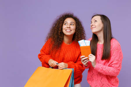 Pensive european african american women friends in sweaters isolated on violet purple background. People lifestyle concept. Hold package bag with purchases after shopping, passport tickets looking up.