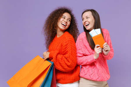 Laughing european african american women friends isolated on violet purple background. People lifestyle concept. Hold package bag with purchases after shopping, passport tickets looking at each other.