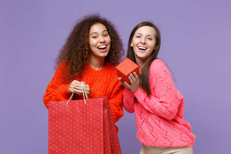 Cheerful european african american women friends in sweaters isolated on violet purple background. People lifestyle concept. Hold package bag with purchases after shopping, red present box with gift.