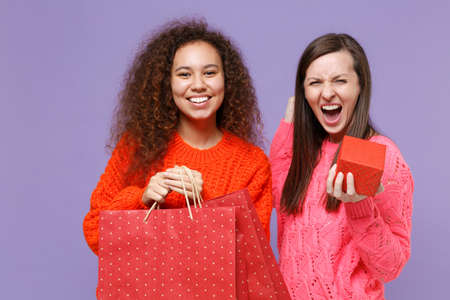 Happy european african american women friends isolated on violet purple background. People lifestyle concept. Hold package bag with purchases after shopping present box with gift doing winner gesture. Imagens