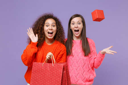Excited european african american women friends isolated on violet purple background. People lifestyle concept. Hold package bag with purchases after shopping, throwing up red present box with gift. Imagens