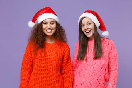 Smiling european african american women friends in knitted sweaters, Christmas hat isolated on violet purple background. Happy New Year celebration holiday concept. Mock up copy space. Looking camera.