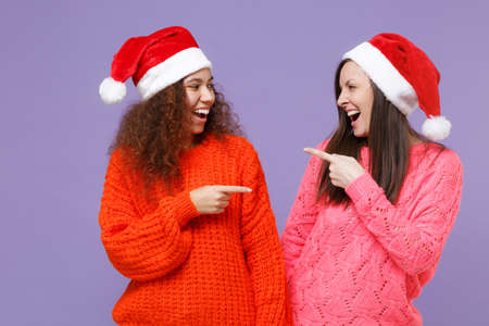 Laughing european african american women friends in Christmas hat isolated on violet purple background. Happy New Year celebration holiday concept. Mock up copy space. Pointing fingers at each other.