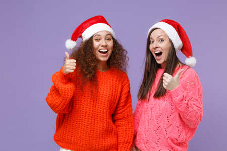 Funny european african american women friends in knitted sweaters, Christmas hat isolated on violet purple background. Happy New Year celebration holiday concept. Mock up copy space. Showing thumb up. Imagens