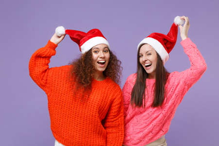 Laughing two young european african american women friends in knitted sweaters isolated on violet purple background. Happy New Year celebration holiday concept. Mock up copy space. Hold Christmas hat.