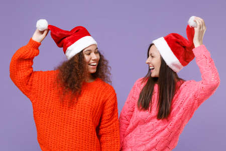 Cheerful two young european african american women friends in knitted sweaters isolated on violet purple background. Happy New Year celebration holiday concept. Mock up copy space. Hold Christmas hat. Imagens