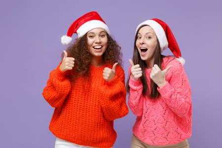 Amazed european african american women friends in knitted sweaters Christmas hat isolated on violet purple background. Happy New Year celebration holiday concept. Mock up copy space. Showing thumb up. Imagens