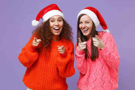 Laughing european african american women friends in Christmas hat isolated on violet purple background. Happy New Year celebration holiday concept. Mock up copy space. Point index fingers on camera. Imagens