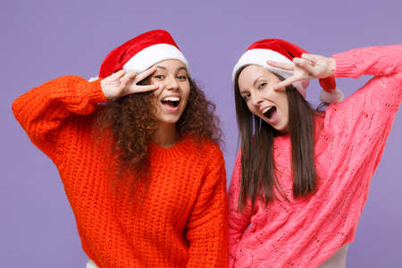 Cheerful european african american women friends in sweaters Christmas hat isolated on violet purple background. Happy New Year celebration holiday concept. Mock up copy space. Showing victory sign.