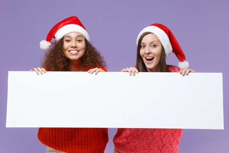 Funny european african american women friends in Christmas hat isolated on violet purple background. Happy New Year celebration holiday. Mock up copy space. Hold blank sign board with place for text. Imagens