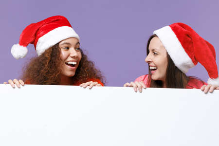 Joyful two european african american women friends in Christmas hat isolated on violet purple background. Happy New Year holiday concept. Mock up copy space. Hold blank sign board with place for text.