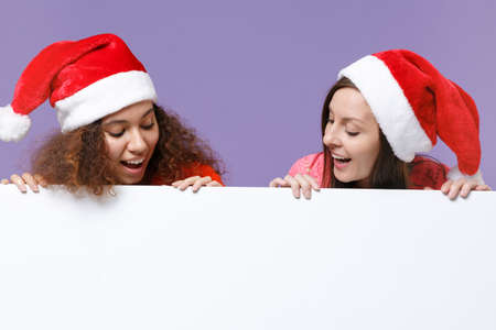 Curious european african american women friends in Christmas hat isolated on violet purple background. Happy New Year holiday concept. Mock up copy space. Hold blank sign board with place for text. Imagens