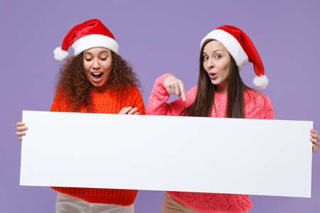 Amazed european african american women friends in Christmas hat isolated on violet purple background. Happy New Year holiday concept. Mock up copy space. Hold blank sign board with place for text.