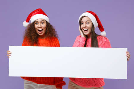 Surprised european african american women friends in Christmas hat isolated on violet purple background. Happy New Year holiday concept. Mock up copy space. Hold blank sign board with place for text. Imagens