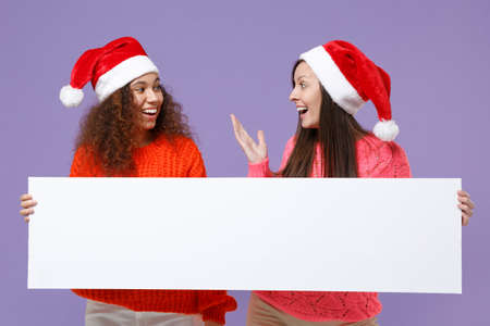 Excited european african american women friends in Christmas hat isolated on violet purple background. Happy New Year holiday concept. Mock up copy space. Hold blank sign board with place for text.