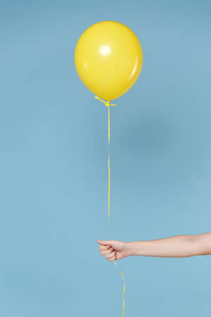 Close up cropped photo of female hold in hands yellow air balloon isolated on blue wall background in studio. Copy space advertising mock up. Birthday holiday party, people emotions concept. Imagens