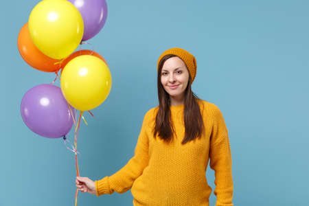 Smiling young woman girl in sweater hat posing isolated on blue background studio portrait. Birthday holiday party, people emotions concept. Mock up copy space. Celebrating hold colorful air balloons.