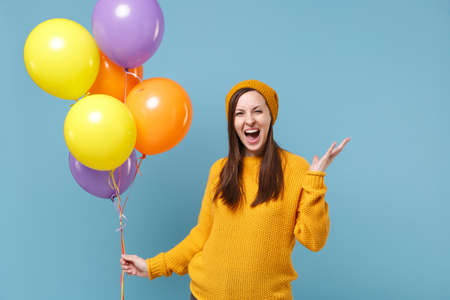 Cheerful young woman girl in sweater hat posing isolated on blue background studio portrait. Birthday holiday party people emotions concept. Mock up copy space. Celebrating hold colorful air balloons.