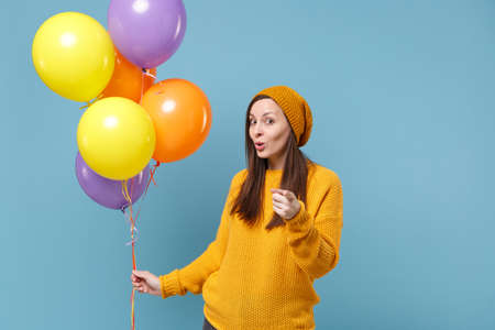 Young woman in sweater hat posing isolated on blue background. Birthday holiday party people emotions concept. Mock up copy space. Celebrating hold colorful air balloons point index finger on camera.