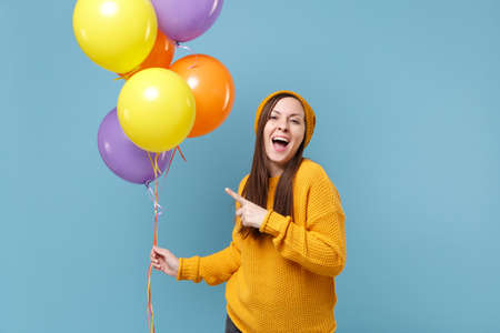 Funny young woman in sweater hat posing isolated on blue background. Birthday holiday party people emotions concept. Mock up copy space. Celebrating hold colorful air balloon point index finger aside. Imagens
