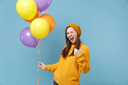 Cheerful young woman in sweater and hat posing isolated on blue background. Birthday holiday party people emotions concept. Mock up copy space. Celebrating hold colorful air balloons showing thumb up.