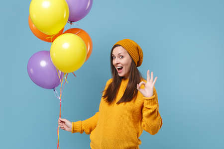 Excited young woman in sweater and hat posing isolated on blue background. Birthday holiday party people emotion concept. Mock up copy space. Celebrating hold colorful air balloons showing OK gesture.