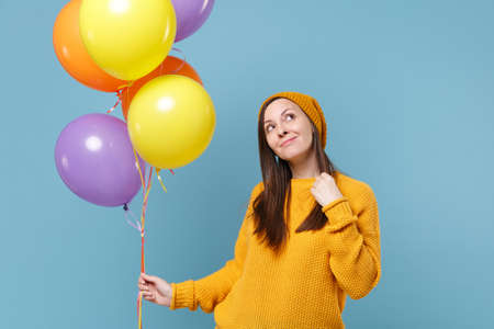 Pensive young woman girl in sweater and hat posing isolated on blue background. Birthday holiday party people emotions concept. Mock up copy space. Celebrating hold colorful air balloons looking up.