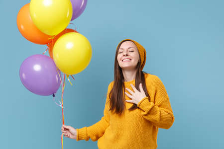 Happy young woman girl in sweater hat posing isolated on blue background. Birthday holiday party people emotions concept. Mock up copy space. Celebrating hold colorful air balloons hold hand on chest. Imagens