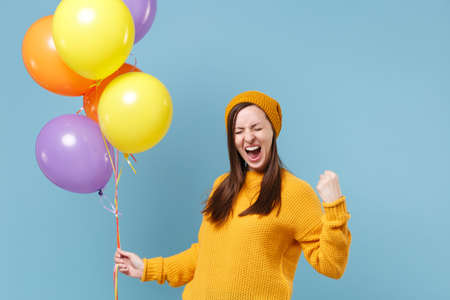 Happy young woman in sweater hat posing isolated on blue background. Birthday holiday party people emotions concept. Mock up copy space. Celebrating hold colorful air balloons doing winner gesture.