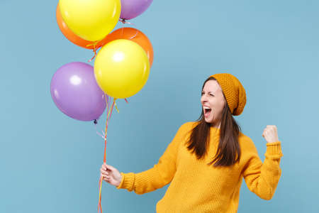 Crazy young woman in sweater hat posing isolated on blue background. Birthday holiday party people emotions concept. Mock up copy space. Celebrating hold colorful air balloons doing winner gesture.
