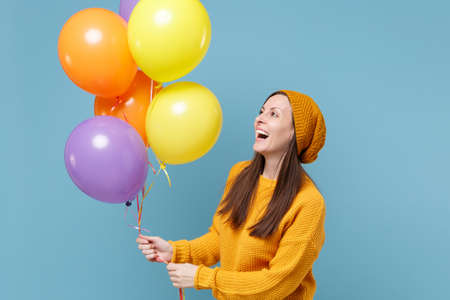 Laughing young woman in sweater and hat posing isolated on blue background. Birthday holiday party people emotions concept. Mock up copy space. Celebrating hold colorful air balloons looking aside.